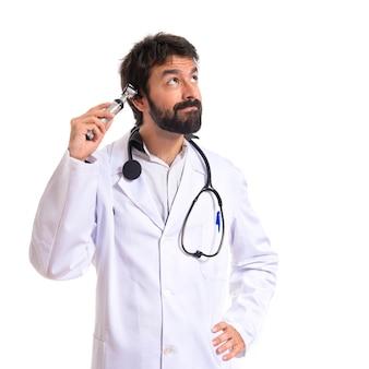 Otorhinolaryngologist with his otoscope over white background