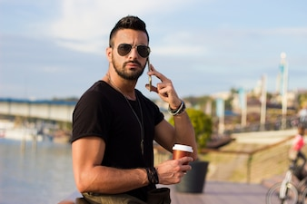 Outdoor portrait of modern young man with mobile phone in the street holding coffee.