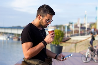 Outdoor portrait of modern young man with mobile phone in the street holding coffee .