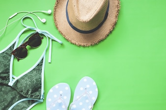 Overhead view of bikini and girl accessories on green color background, Spring summer fashion set