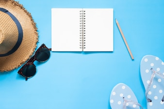 Overhead view of empty notebook with pencil, hat, sunglasses and sandal on blue color background