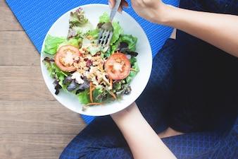 新鮮なサラダ、健康的な食べて、働くコンセプトを食べるヨガの女性のオーバーヘッドビュー