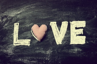 Painted Letters LOVE with Red Heart on Old Wooden Chalkboard Bac