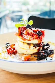 Pancakes with mixed berry fruit in white plate