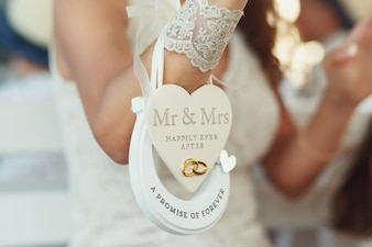 Paper heart 'Mr & Mrs happily ever after' and horseshoe 'A promise of forever' hang on bride's wirst