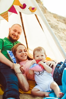Parents holds little son on their arms lying under the tent
