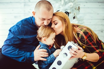 Parents kissing baby boy holding gift