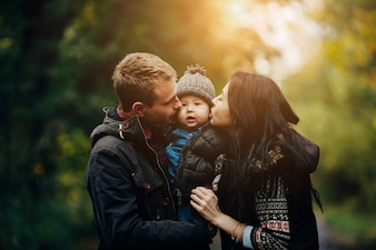 Parents kissing kid in park