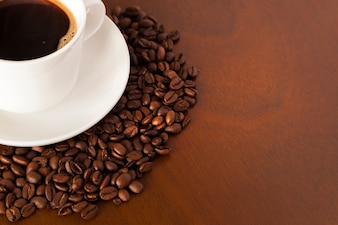 Partial view of coffee cup and beans on wooden table