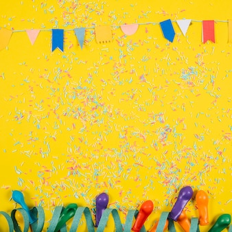Party composition with confetti and balloons