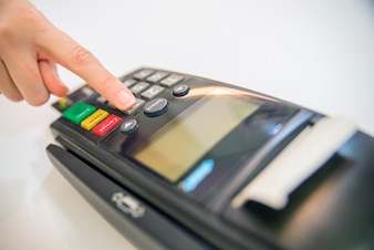 Payment card in a bank terminal. The concept of of electronic payment. hand pin code on pin pad of card machine or pos terminal good photo