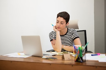 Pensive businesswoman looking at her laptop