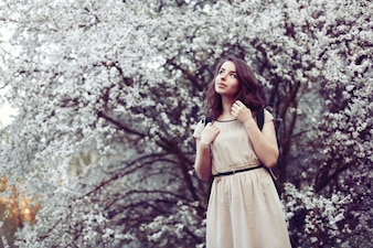 Pensive girl wearing dress with tree background