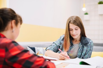 Pensive girls writing at desk