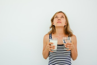 Pensive Lady Holding Glasses of Water and Milk