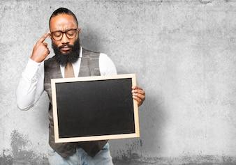 Pensive man holding a blackboard