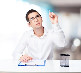 Pensive man with a ball-point pen and check table