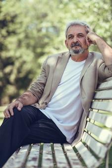 都市の公園のベンチに座っている幸せな成熟した男。