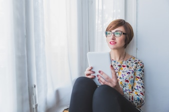 Pensive woman holding a tablet