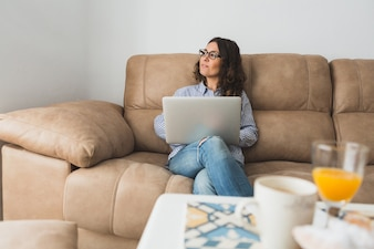 Pensive woman with laptop sitting on the couch