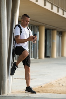 Pensive young athlete texting message during rest