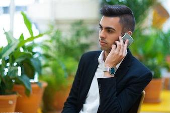 Pensive young entrepreneur talking on phone