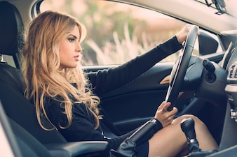 Pensive young woman driving her car