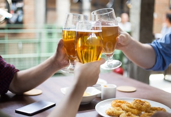 People Clinking Glasses of Beer in Pub