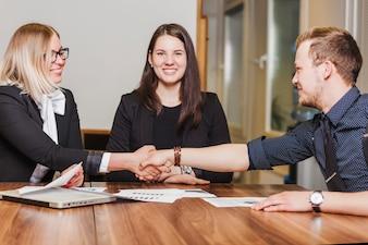 People sitting at desk smiling shaking hands