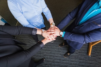 People standing in office holding hands together