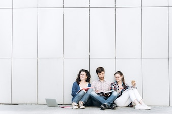 People with books and gadgets sitting on floor near the wall. Education social media concept.
