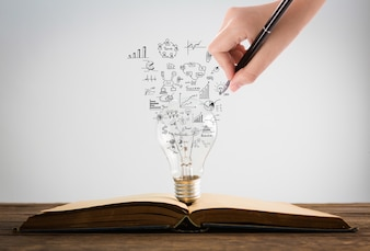 Person drawing symbols coming out of a light bulb on top of a book