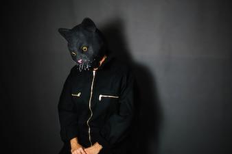 Person in cat mask in dark room