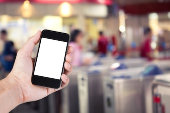 Person using smartphone white screen holder on hand with  blurred background of people walking past ticket machines in electrical train station.