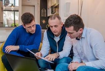 Photo of a group of friends working on some new ideas at home. Young business people are studying documents, discussing ideas and smiling while working at home