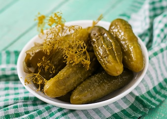 Pickled cucumbers on a light wooden background
