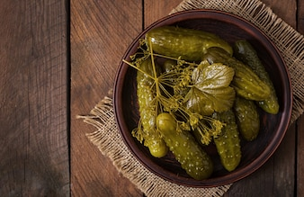 Pickled cucumbers on wooden background