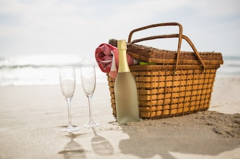 Picnic basket, champagne bottle and two glasses on sand