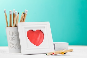 Picture with a red heart and pencils behind