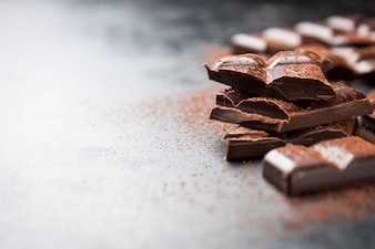 Pieces of chocolate on a wooden table and cacao sprinkled