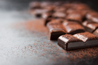 Pieces of chocolate tablet on a black wooden table and cacao sprinkled on top