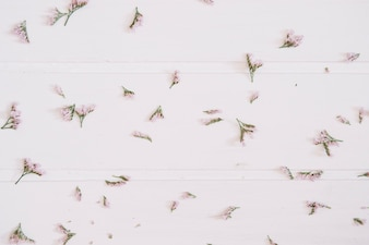 Pieces of lilac flowers over a white wooden top