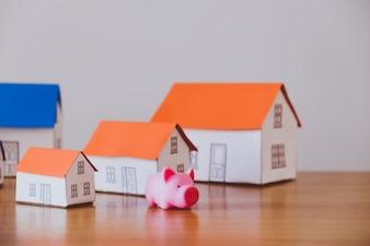 豚のお金箱と木製の壁の背景に紙の家
