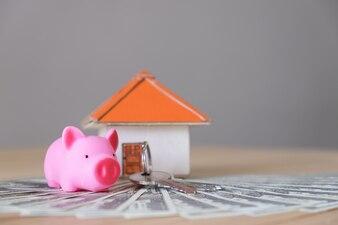 豚のお金箱と木製の壁の背景にキーとペーパーハウス
