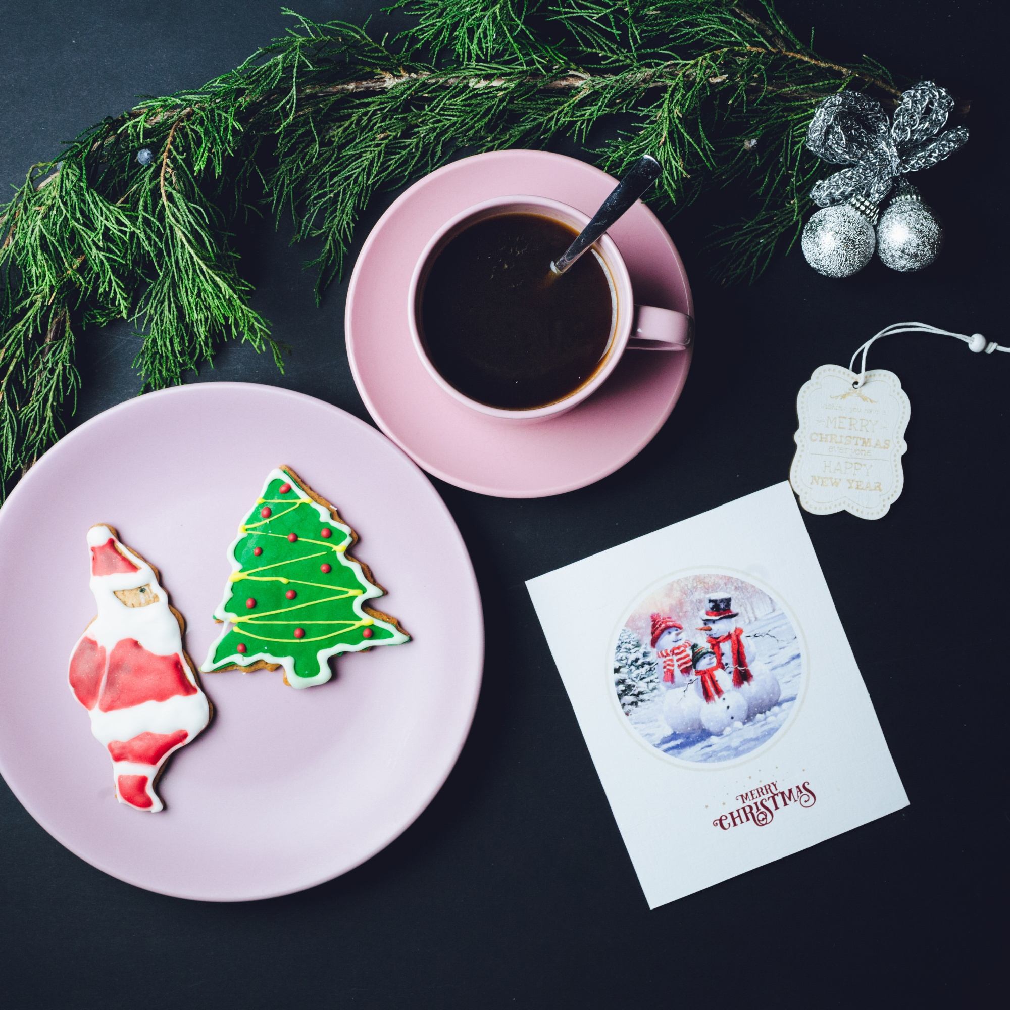 Pink cup of coffee, plate with Christmas gingerbreads and postcard lie on black table