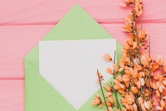 Pink surface with blank paper and floral decoration