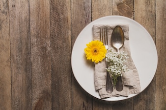 Plate with cutlery and flower on wooden table