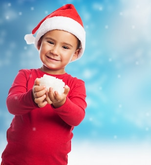 Playful boy with santa claus hat and snow in hands