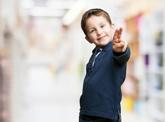 Playful child pointing with two fingers