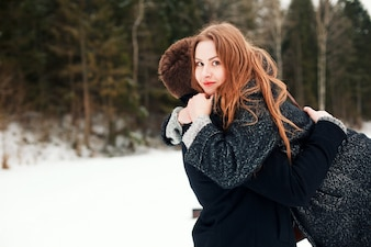 Playful young couple spending the day in the snowy field